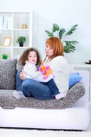 tickling:  Young mother lying on the sofa and playing with her happy loving little daughter – indoor Stock Photo