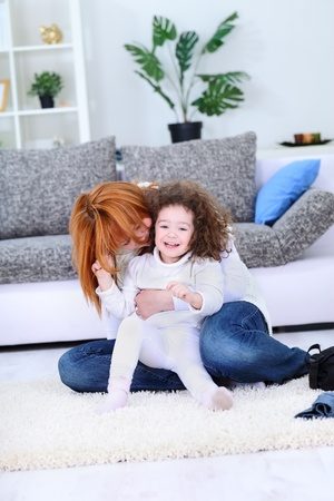 tickling: Beautiful happy family of young mother and her little pretty daughter – indoor