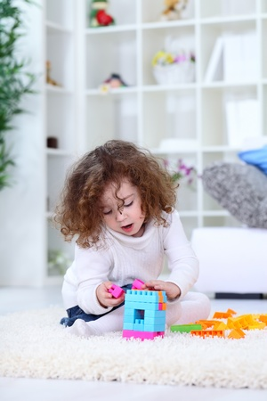 Little girl playing with toys on floor in living room  photo