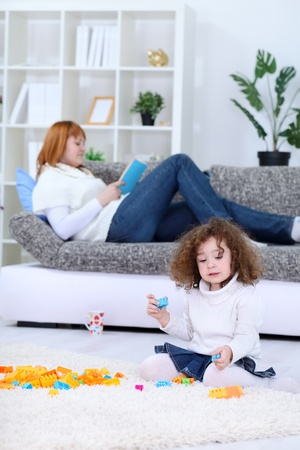 Cute girl playing while her mom is in the background on sofa photo