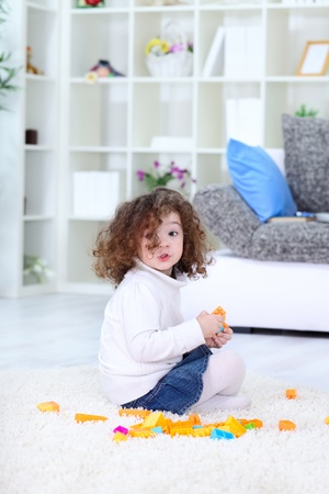 concentration:  beautiful little girl playing with blocks on floor