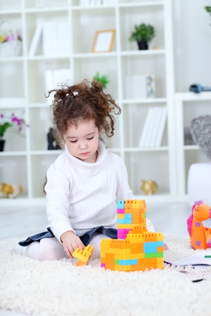 Little girl playing with toys at home  photo