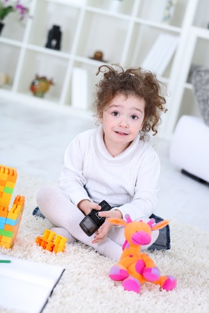 Portrait of a little girl playing with colorful cubes toys at home photo