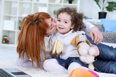 Adorable girl and mother at home, mom kissing her daughter photo