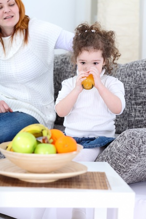little girl drinking tasty orange juice in living room  Stock Photo