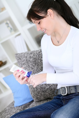 young woman relaxing in living room and using hand cream Stock Photo - 13092995