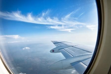 멋진 푸른 하늘과 날개의 비행 중 항공기 창을 통해 찾고 스톡 콘텐츠