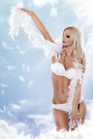 young woman in white lingerie as angel on the clouds photo