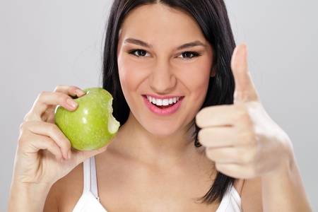 Young woman with green apple and showing thumb up, healthy eating  photo