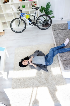 Young girl lying on floor in living room and listening music through smart phone Stock Photo - 13524723