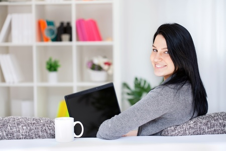 using the laptop: Portrait of a happy young woman sitting on sofa using laptop Stock Photo