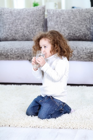 Little girl drinking water at home photo