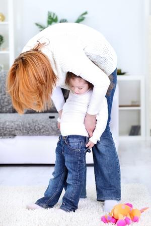niños vistiendose: riendo medias madre vistiendo a su niña Foto de archivo