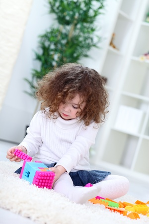 Child playing with cube toys, concentrate on connecting blocks Stock Photo - 13524615
