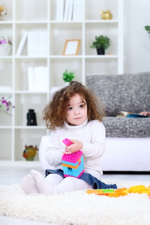Little girl playing with cubes blocks photo