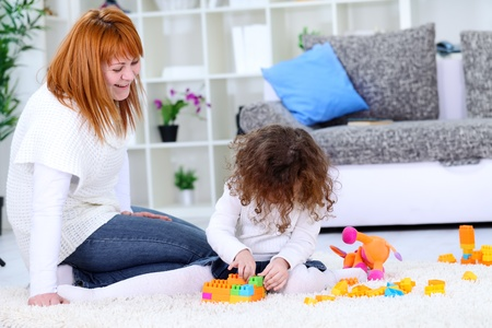 Laughing mother playing with her little daughter photo