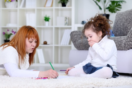 mother painting while  little surprises daughter looking it  photo