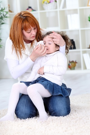 Mother wiping sick daughter's nose with tissue photo