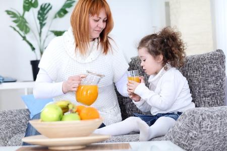 mother serving orange juice her daughter  photo