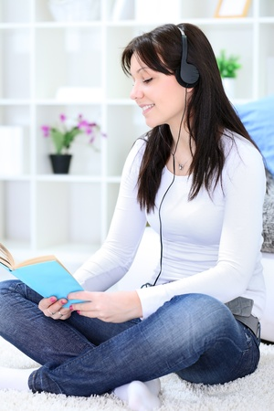 Young girl reading book and listening music, enjoying time photo