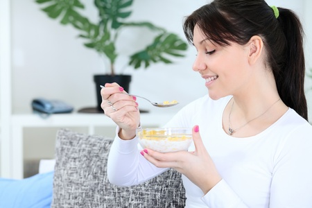 cornflakes:  smiling woman eating cornflakes for breakfast Stock Photo
