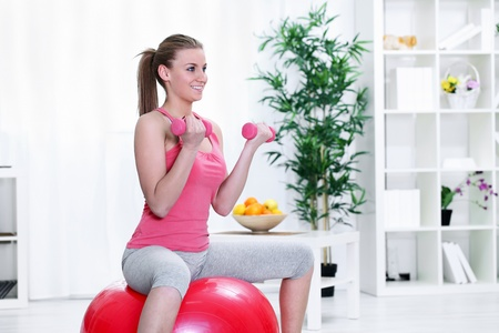 Cute female sitting on a fitness ball and lifting dumbbells photo