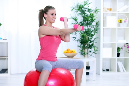Young woman doing fitness exercise with dumbbell and sitting on fitness ball photo