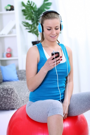 Young girl siting on fit ball and choosing music for exercise, preparing for practice Stock Photo - 13524349