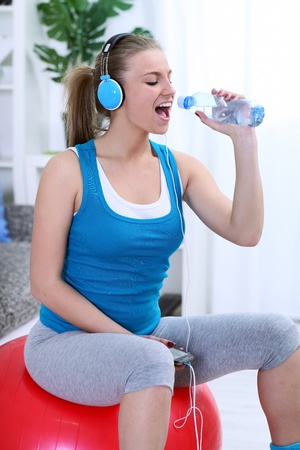 Teenager girl having fun during exercise, singing in bottle photo