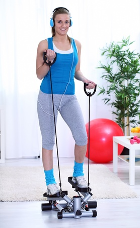 home trainer:  young woman exercising on stepper trainer at home