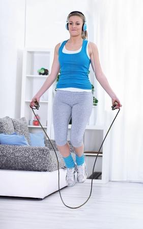 saltar la cuerda: Joven mujer haciendo ejercicios con una cuerda de saltar. Foto de archivo