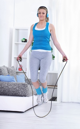 Young woman doing exercises with a jumping rope. photo