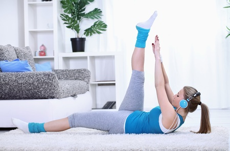 Teenager girl training abdominals at home, full length, side view photo