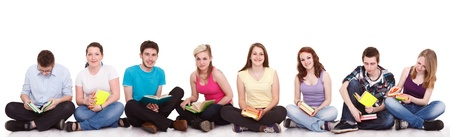 group of teenagers: group of young students sitting on the floor  with books,  isolated on white background