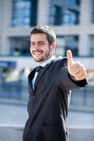 young success businessman showing thumbs-up sign, outdoor Stock Photo - 13888095