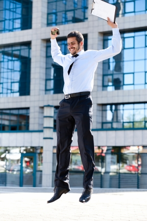 Happy young successful businessman jumping against office building  photo