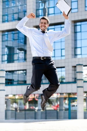 Jumping happy businessman over office buildings photo