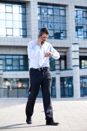 businessman on  phone and checking his watch in front of his office building, running late  photo