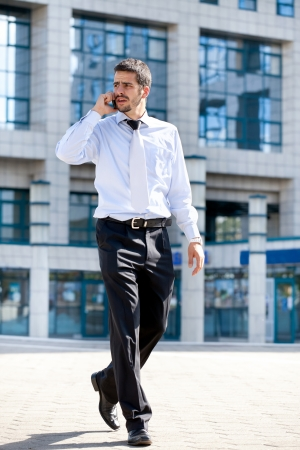 businessman talking on his cellphone while walking outdoors in front of a modern office building photo
