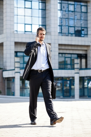 businessman talking on phone while walking outdoors of a modern office building photo