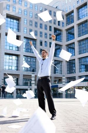 giovane uomo d'affari in piedi davanti il ??suo ufficio edificio e gettare via le sue carte, mai sentito così bene Archivio Fotografico