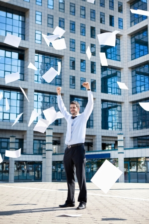 Businessman throwing paperwork in air against office building photo