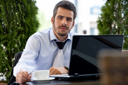 Young handsome businessman working on laptop,  outdoor photo