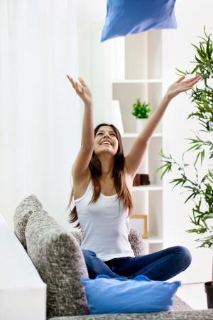 throw cushion:  Teenager girl throwing  pillow into the air, having fun  Stock Photo