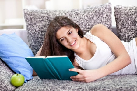 Pretty teen girl reading book and lying on couch in living room  photo