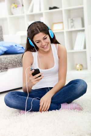 Girl listening to music while sitting on the floor at home  photo