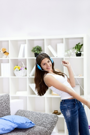 Teenager girl with smart phone dancing and listening music photo