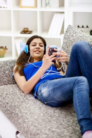 teenager girl lying on sofa and listening music photo
