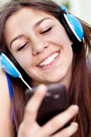 Close up of laughing teenager girl with smartphone  Stock Photo - 13888233