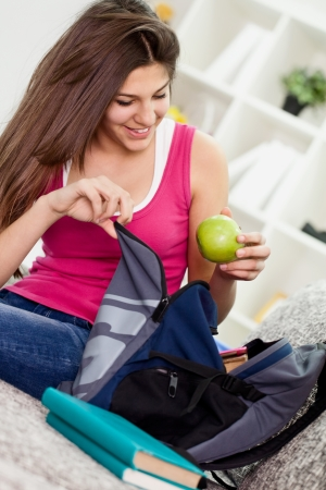 Teen girl  packing book bag preparing for school. Stock Photo - 13888240